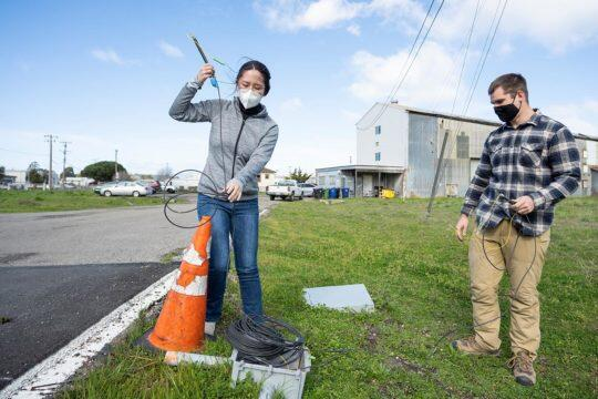 Graduate students Ruonan Ou and Peter Hubbard, from left, check on fiber optic cables installed beneath a paved road at Richmond Field Station. The cables are so sensitive that when a dog walks over the pavement, they can pick up tiny deformations in the